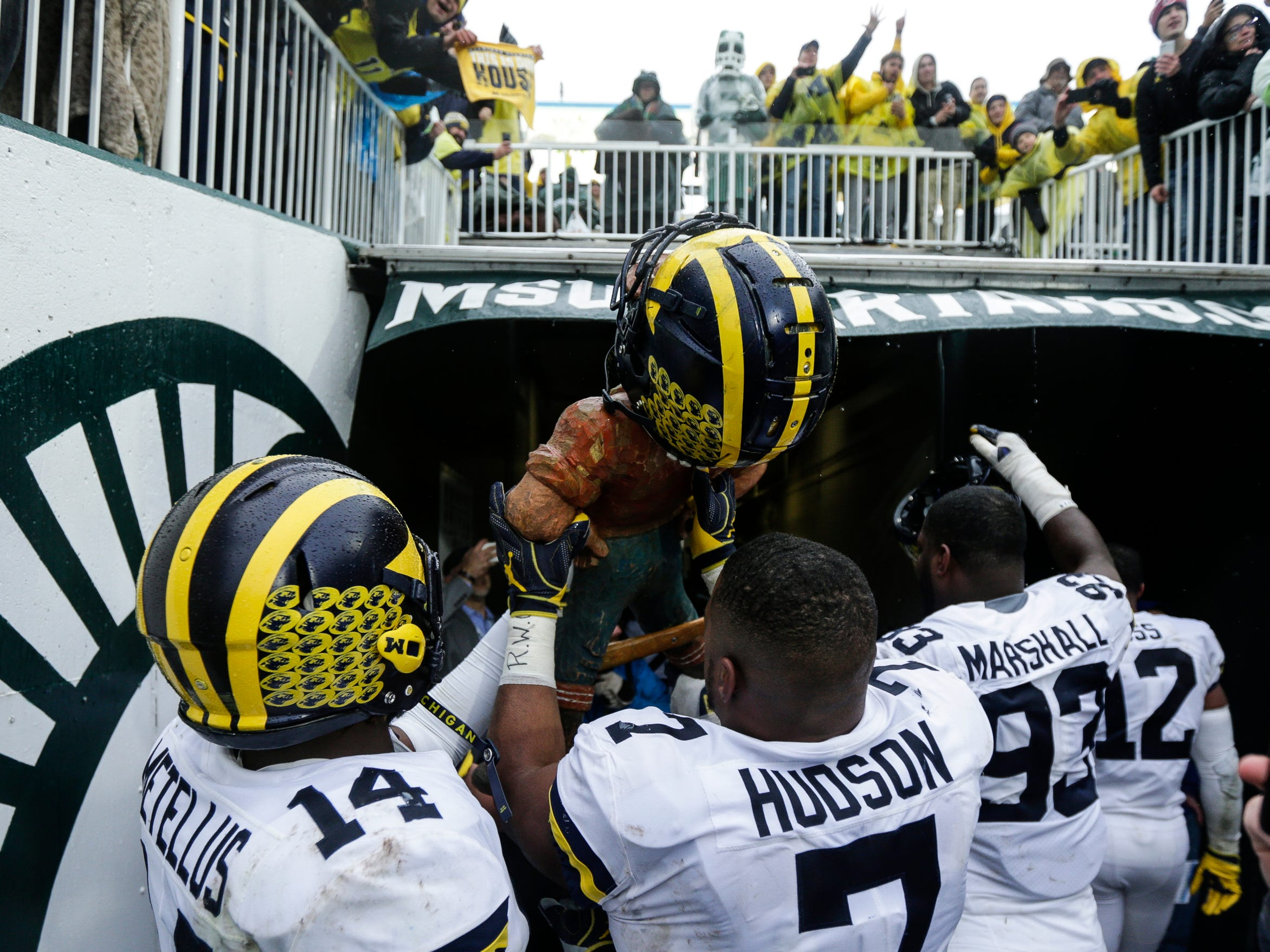 Michigan lienbacker Khaleke Hudson raises the Paul Bunyan Trophy to celebrate the 21-7 victory over Michigan State in the tunnel at Spartan Stadium in East Lansing, Saturday, Oct. 20, 2018.