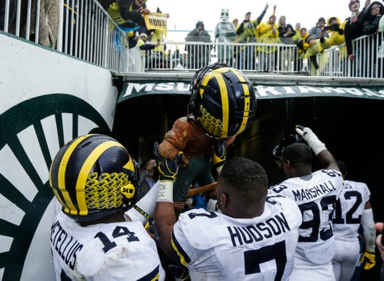 Michigan linebacker Khaleke Hudson raises the Paul Bunyan Trophy to celebrate the 21-7 victory over Michigan State in the tunnel at Spartan Stadium in East Lansing, Saturday, Oct. 20, 2018.