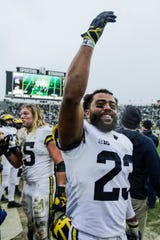 Michigan safety Tyree Kinnel celebrates from the sideline during the second half against Michigan State at Spartan Stadium in East Lansing, Saturday, Oct. 20, 2018.