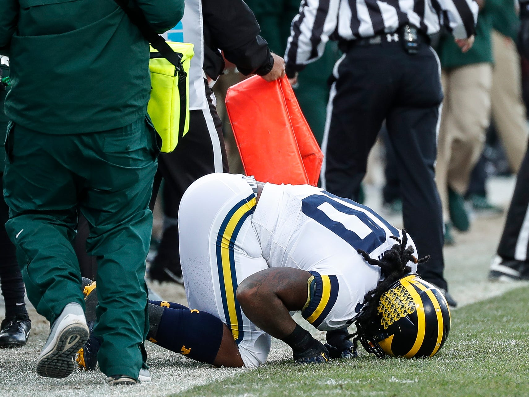 Michigan linebacker Devin Bush stays on the ground after tackling Michigan State running back LJ Scott during the first half at Spartan Stadium on Saturday, Oct. 20, 2018.