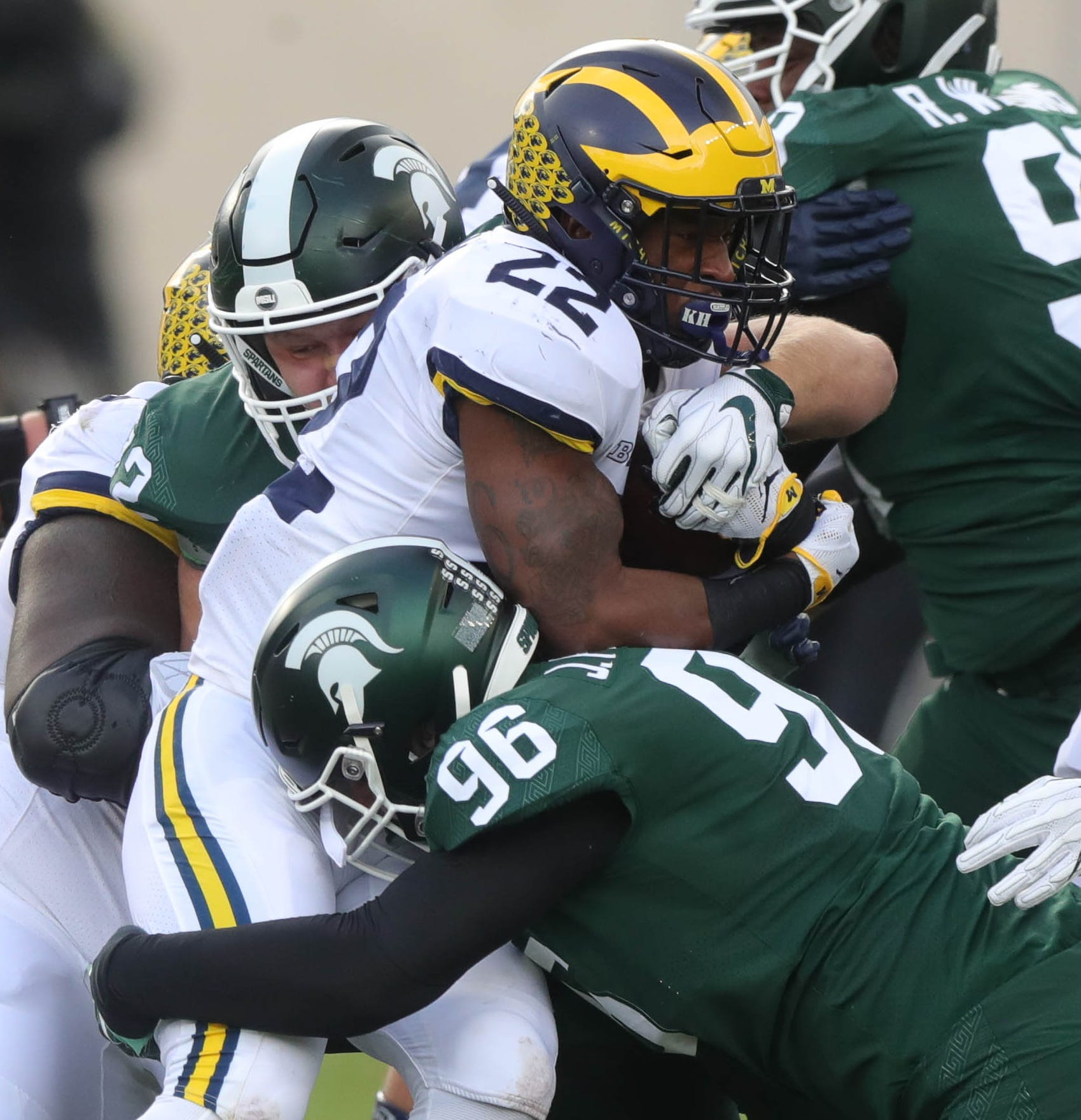 Michigan running back Karan Higdon is tackled by Michigan State defenders during the first half on Saturday, Oct. 20, 2018, at Spartan Stadium.