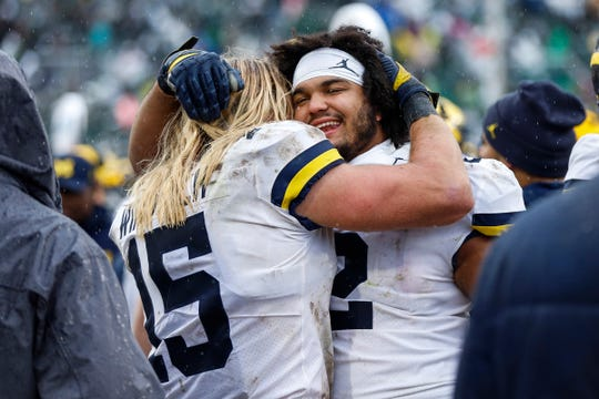 Michigan defensive lineman Carlo Kemp hugs teammate Chase Winovich during the second half at Spartan Stadium last season.
