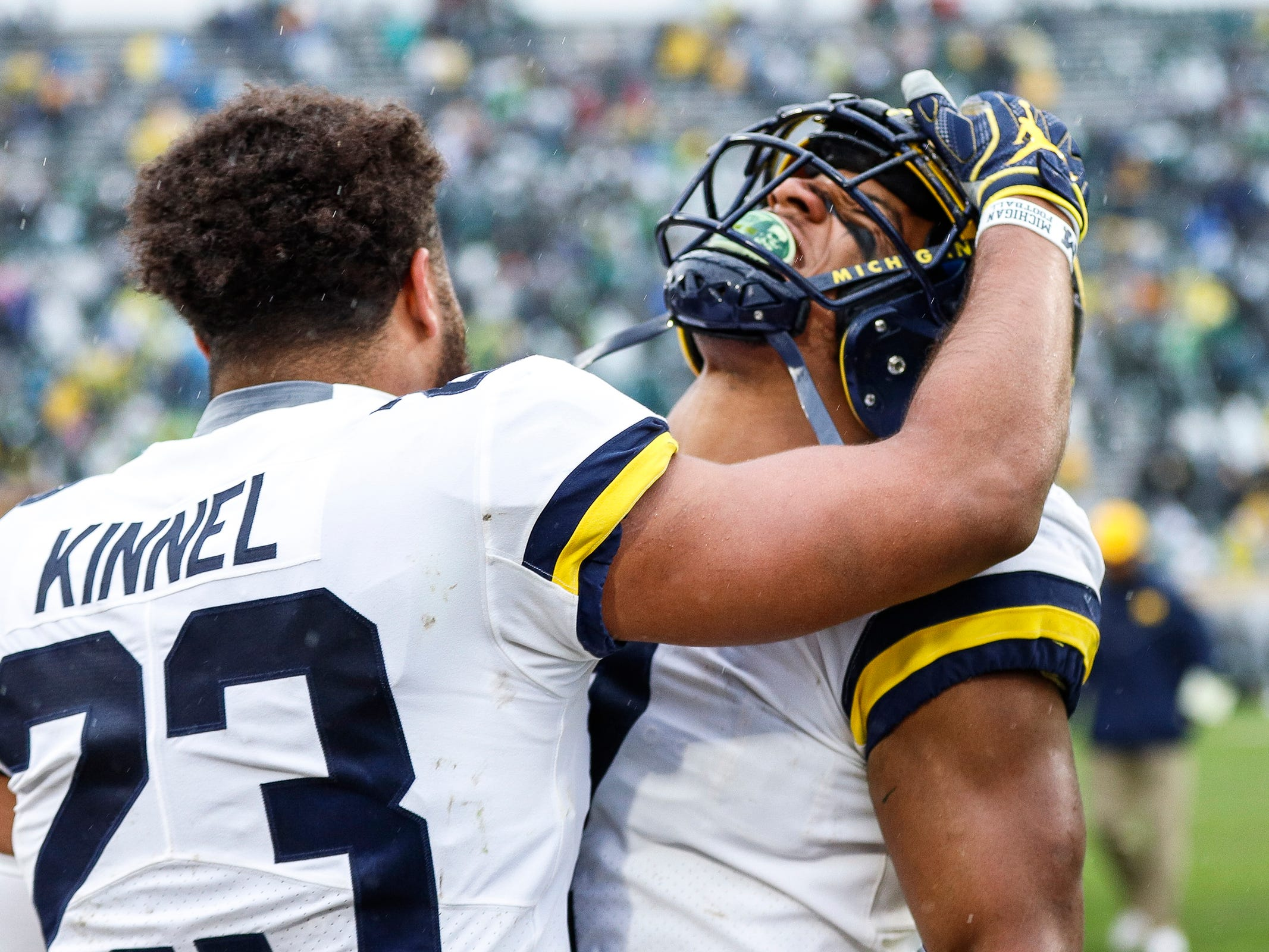 Michigan safety Tyree Kinnel celebrates with linebacker Khaleke Hudson during the second half against Michigan State at Spartan Stadium in East Lansing, Saturday, Oct. 20, 2018.