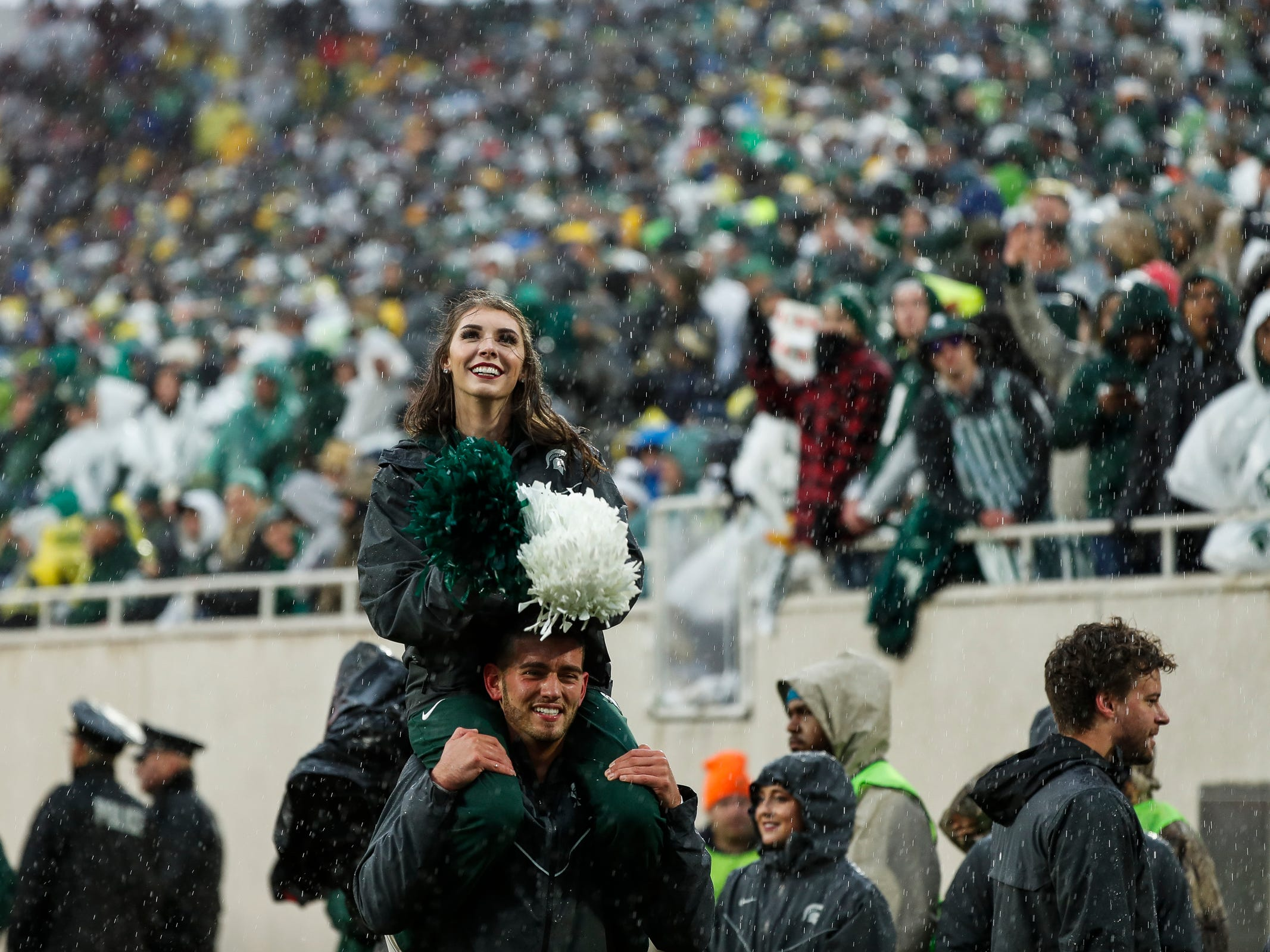 Michigan State cheerleaders enjoy the rain during the second half against Michigan at Spartan Stadium in East Lansing, Saturday, Oct. 20, 2018.