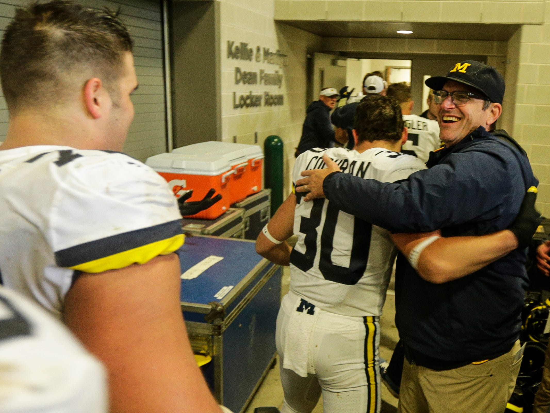 Michigan head coach Jim Harbaugh hugs defensive back Tyler Cochran outside the locker room to celebrate the 21-7 win over Michigan State at Spartan Stadium in East Lansing, Saturday, Oct. 20, 2018.