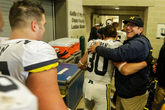 Jim Harbaugh hugs defensive back Tyler Cochran outside the locker room to celebrate the win over Michigan State at Spartan Stadium.
