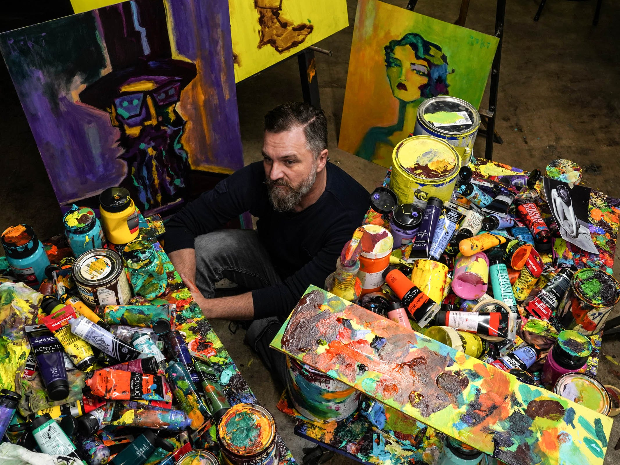 Artist Tony Roko with the tools of his trade at his studio in Plymouth on Friday, October 12, 2018. Roko got his start on the Ford Assembly line and has painted murals for Ford factories and will have a piece featured in Ford's renovation of the former Michigan Central Station in Detroit's Corktown neighborhood.