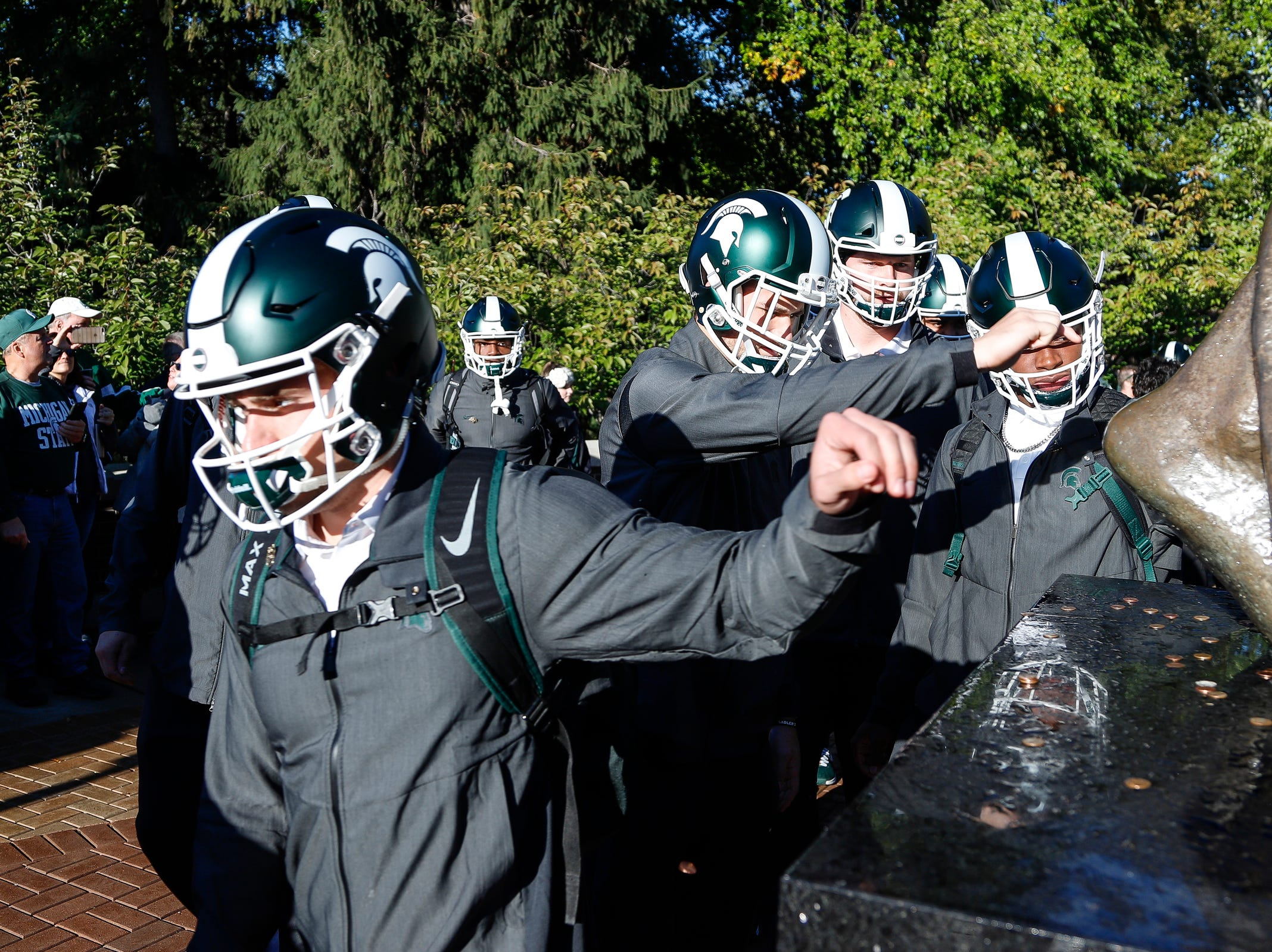 Michigan State football players leave pennies at the Spartan statue at Spartan Stadium in East Lansing before the Michigan game on Sat., October 20, 2018.