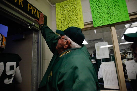 Farmington Hills Harrison head coach John Herrington touches the Harrison sign in the locker room before taking the field against Farmington Friday, October 19, 2018 at Farmington Hills Harrison in Farmington Hills, Mich.