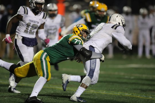 Farmington Hills Harrison's Maverick Hansen tackles Farmington's Delmon Sewell on Oct. 19, 2018 in Farmington Hills.