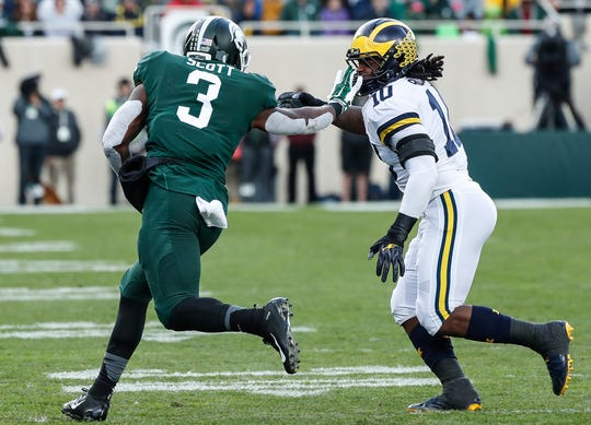 Michigan State running back LJ Scott runs against Michigan linebacker Devin Bush during the first half at Spartan Stadium on Saturday, Oct. 20, 2018.