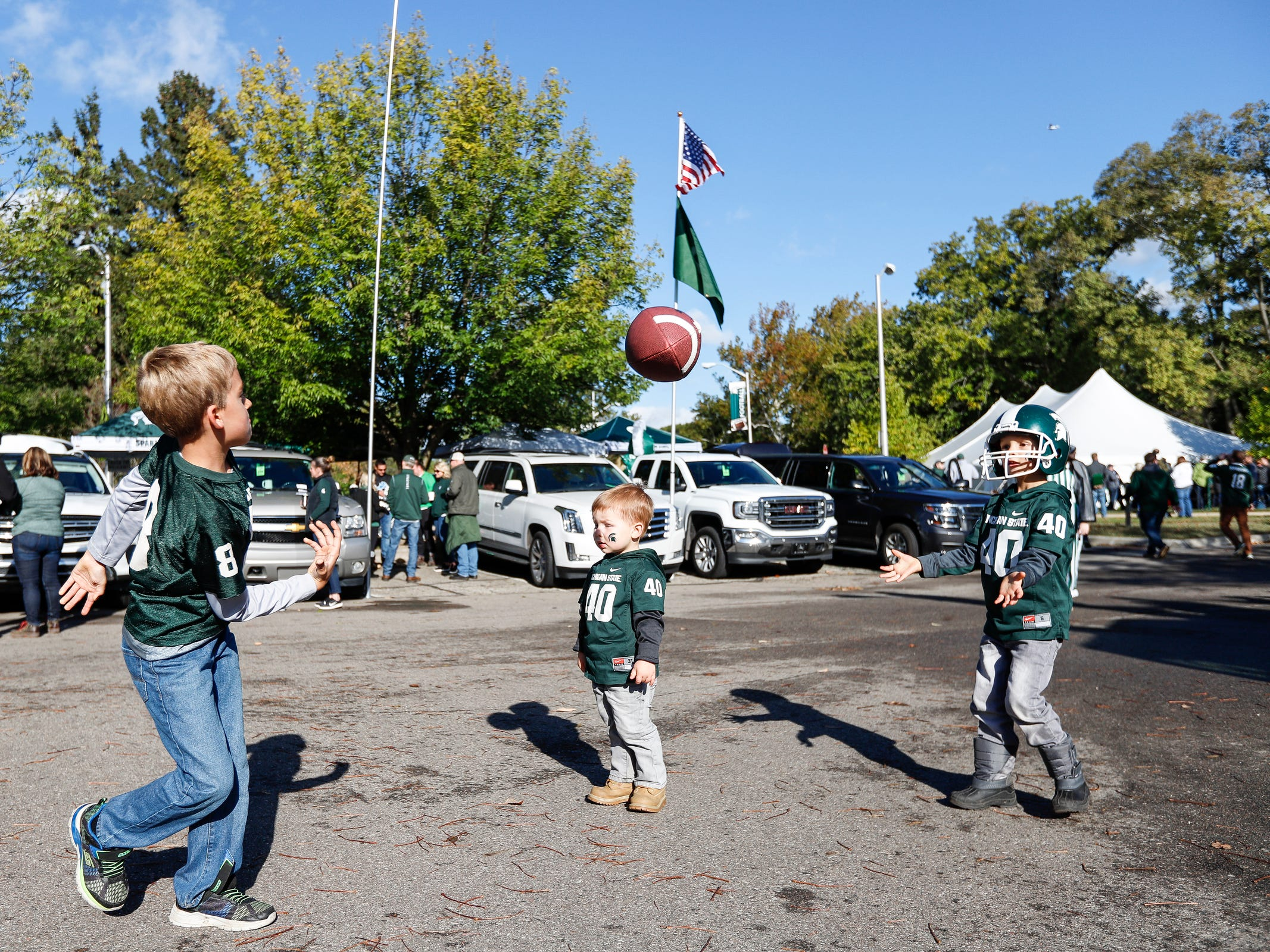 (From left) Lucas Halmekangas, 7, Tyler Spahr, 2, and Aiden Spahr, 5, all of South Lyon, play football while tailgating with parents outside of the Spartan Stadium on Saturday, Oct. 20, 2018.