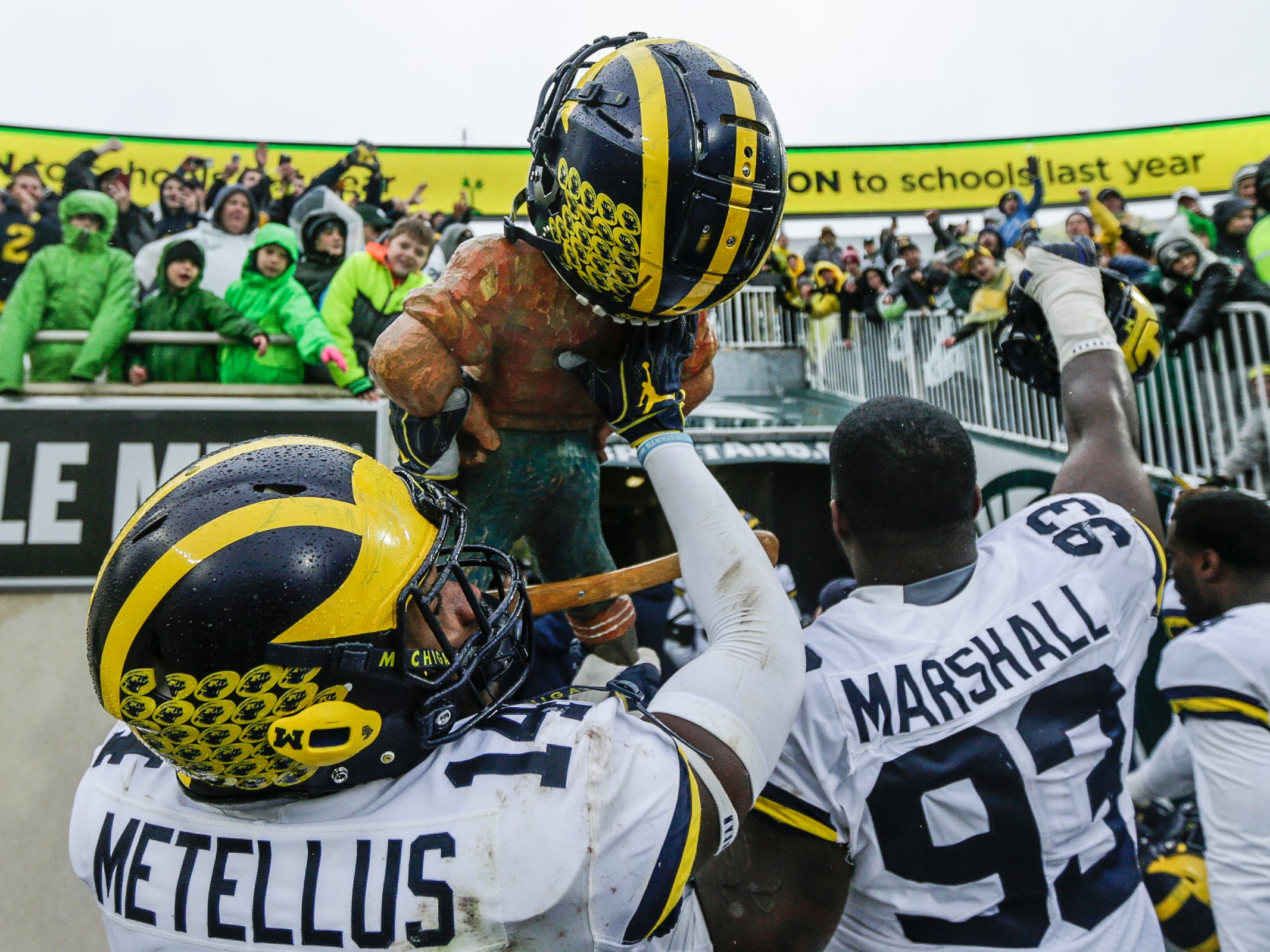 Michigan safety Josh Metellus holds the Paul Bunyan Trophy as he walks into the tunnel at Spartan Stadium in East Lansing, Saturday, Oct. 20, 2018.