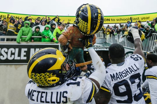 Michigan safety Josh Metellus holds the Paul Bunyan Trophy as he walks into the tunnel at Spartan Stadium.