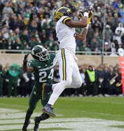 Michigan receiver Nico Collins catches a touchdown against Michigan State cornerback Tre Person during the first half.