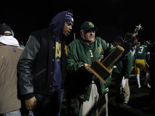 Notre Dame defensive end Khalid Kareem a former  Harrison player and Farmington Hills Harrison head coach John Herrington look at the trophy after the win against Farmington Friday, October 19, 2018 at Farmington Hills Harrison in Farmington Hills, Mich.