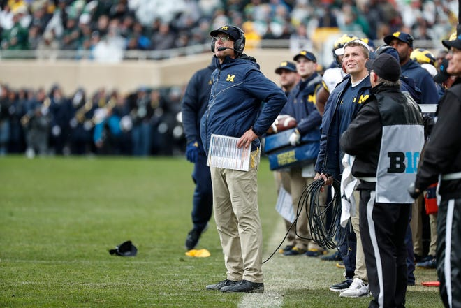 Michigan head coach Jim Harbaugh looks at replay against Michigan State during the second half at Spartan Stadium in East Lansing, Saturday, Oct. 20, 2018.