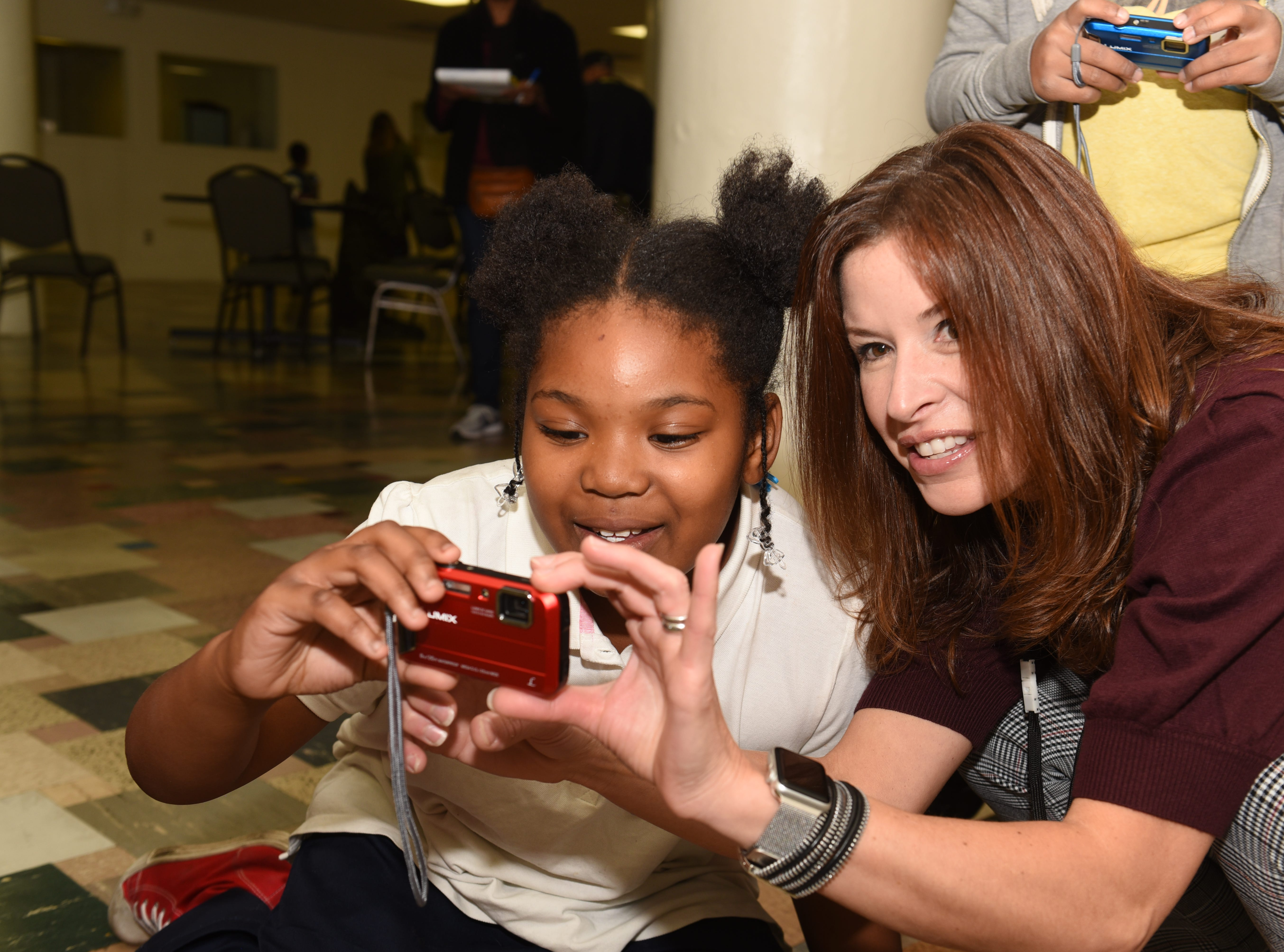 Fox 2 reporter Amy Lange (right) works with Nhyrasia S.  during a photography lesson by Linda Solomon in Detroit on October 20, 2018.