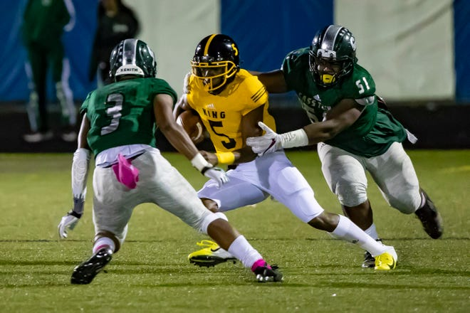 Detroit King's Dequan Finn (5) tries to run the ball between Detroit Cass Tech's Noah Stamps (3) and Duwayne Legette  in the first quarter on Friday.