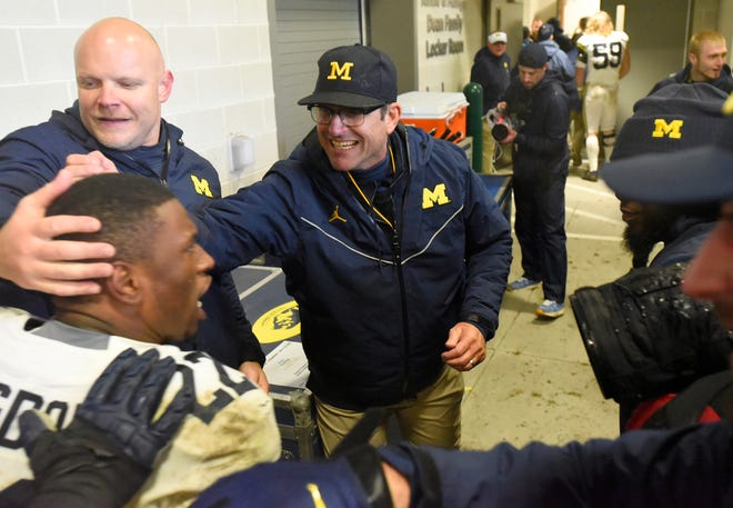 Michigan football head coach Jim Harbaugh hugs running back Karan Higdon outside the locker room Saturday in East Lansing.