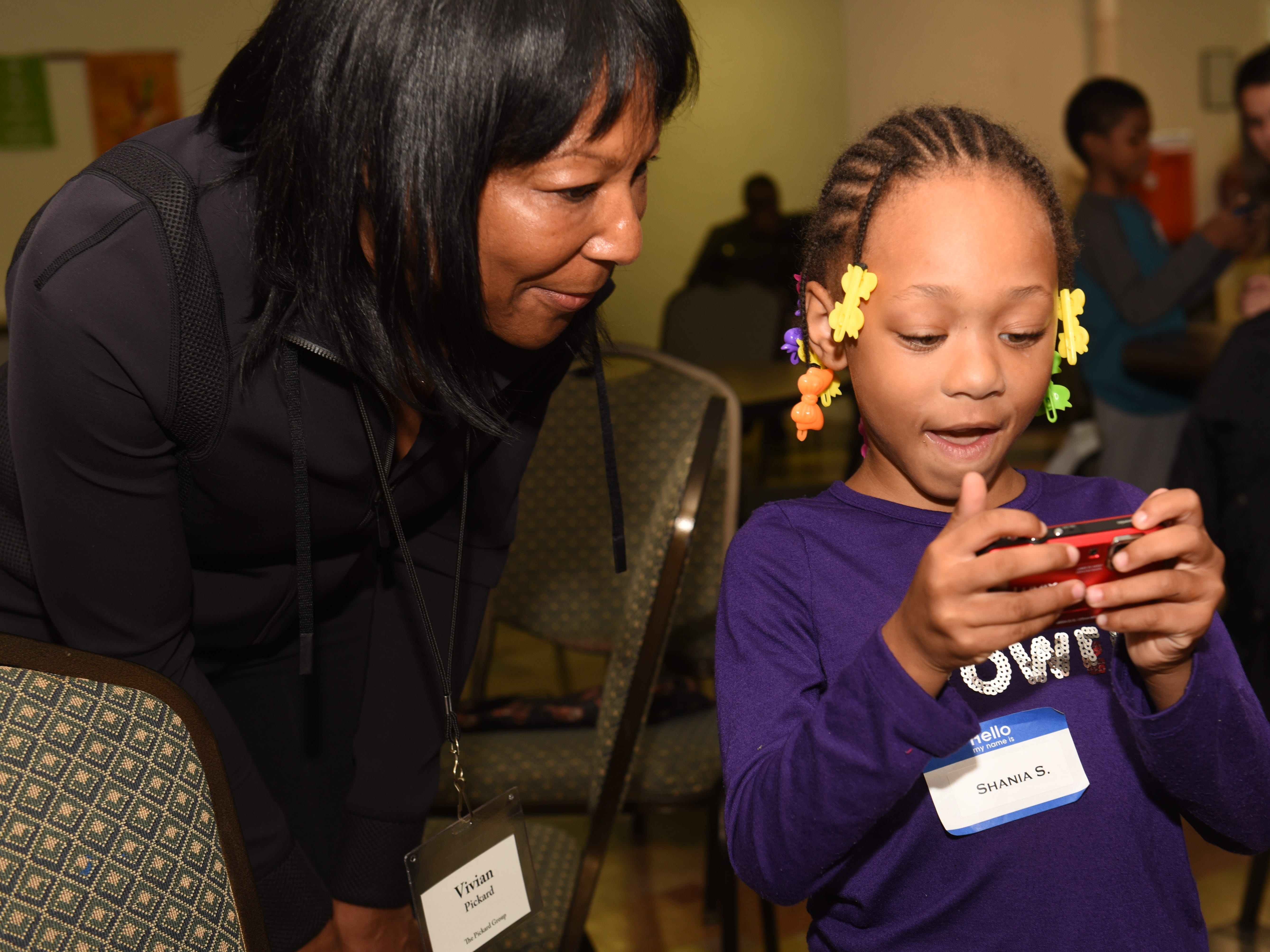 Volunteer mentor Vivian Pickard  (left) assist Shania S. as they view images  in Detroit on October 20, 2018.