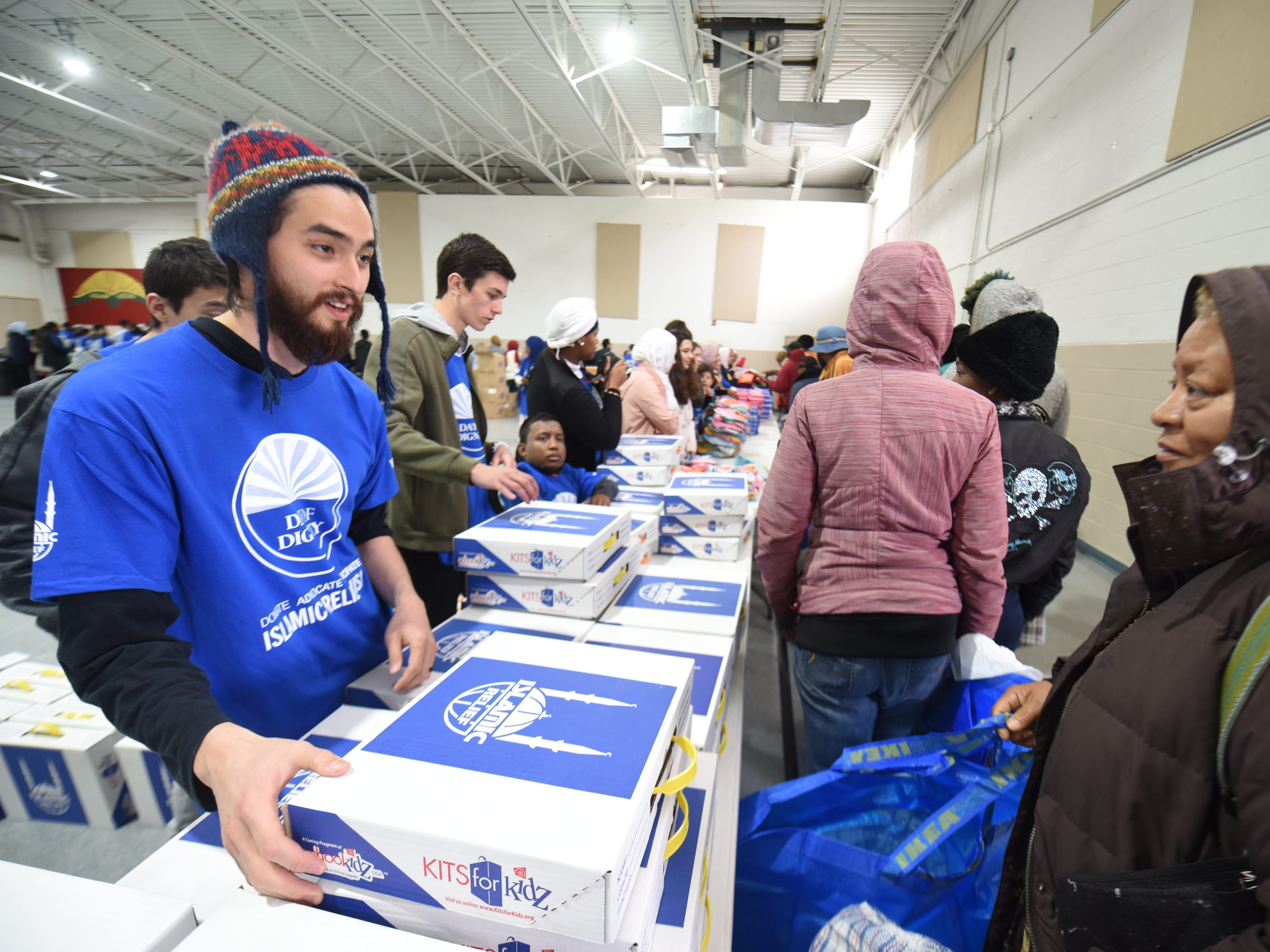 Volunteer Tony Villano (left) assist people during the Islamic Relief USA's Day of Dignity at the Muslim Center Mosque and Community Center in Detroit on Saturday October 20, 2018.