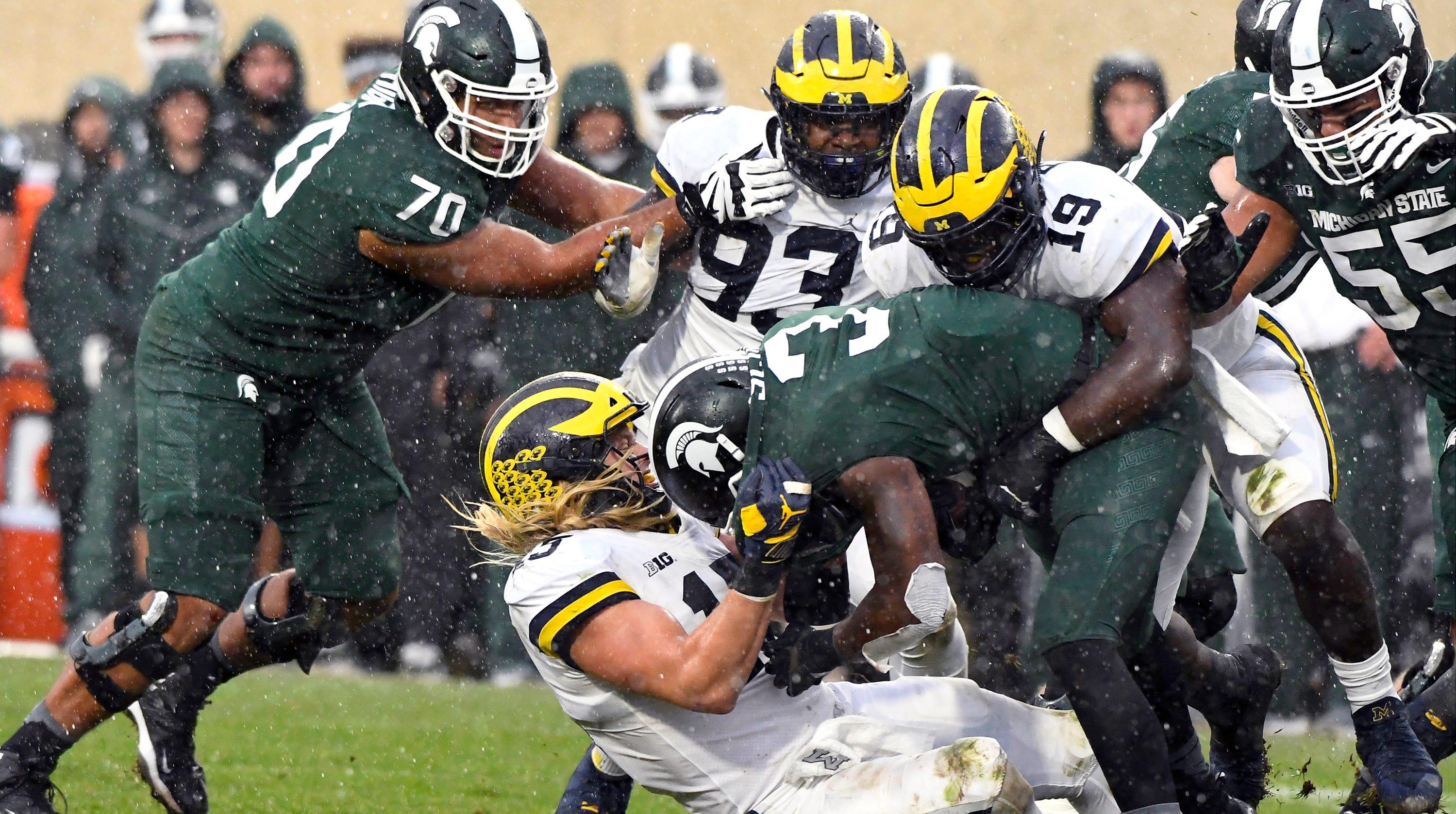 Michigan's Chase Winovich hauls down   Michigan State's LJ Scott in the second half.