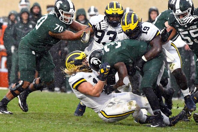 Michigan's Chase Winovich takes down Michigan State's LJ Scott in the second half on Saturday.