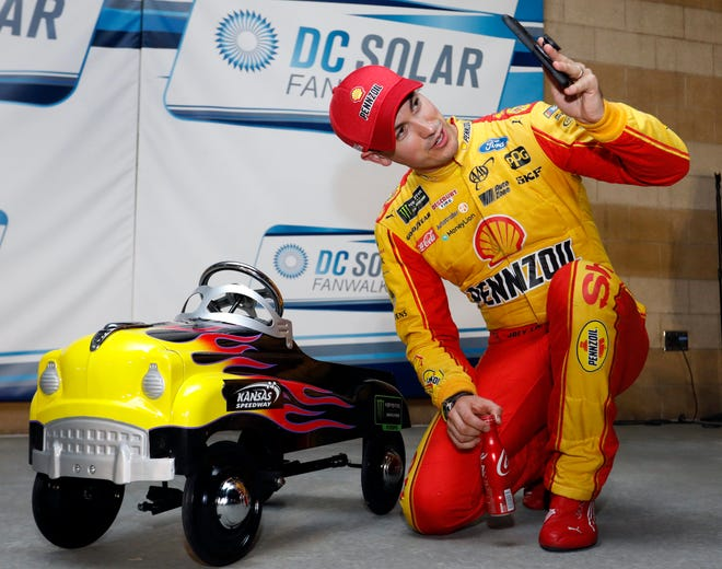 Joey Logano takes a photo with the pole award after qualifying on Friday.