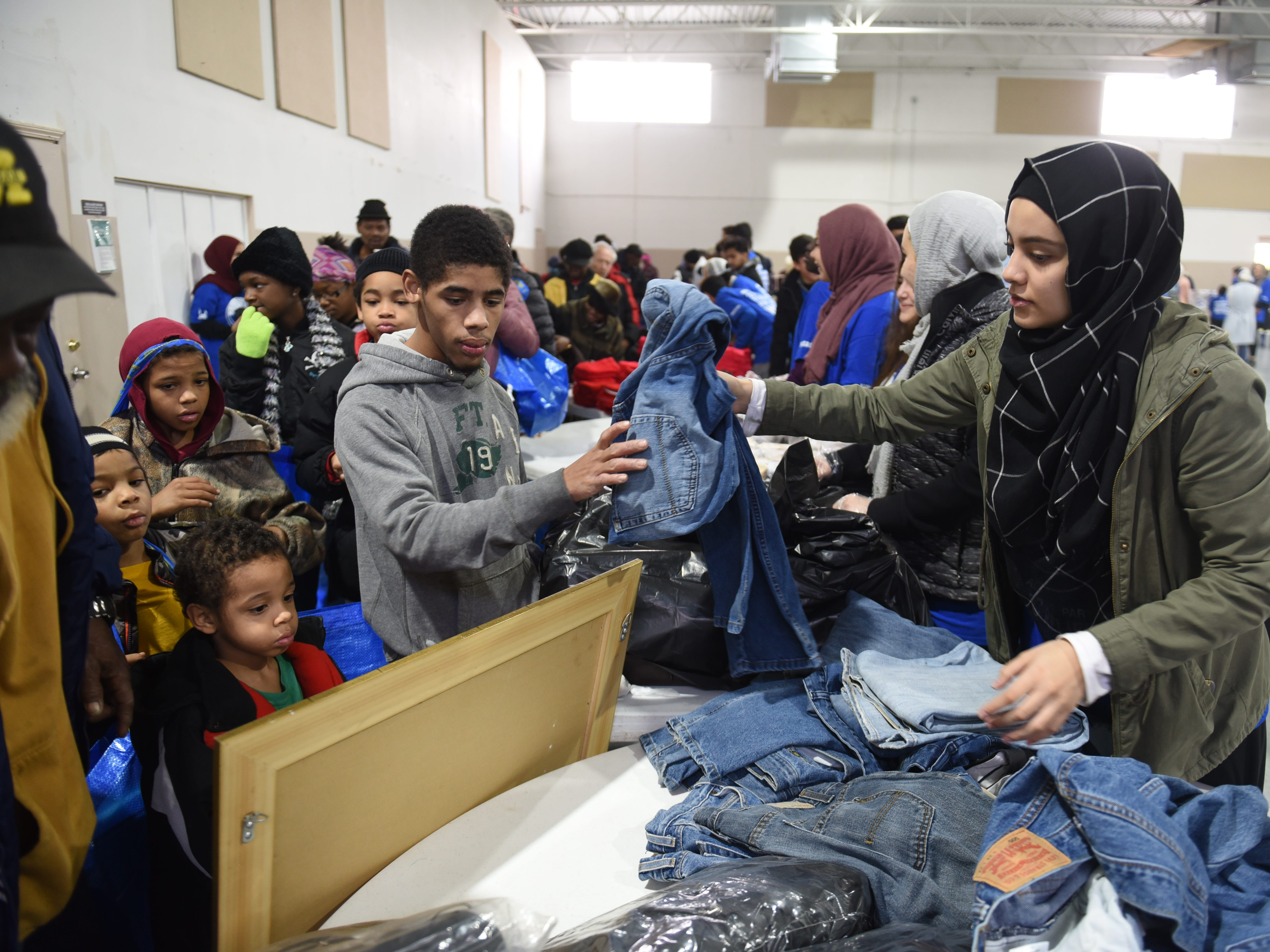 Volunteer Halla Almasmari (right) hands a pair of jeans to a client at the Muslim Center Mosque and Community Center in Detroit.