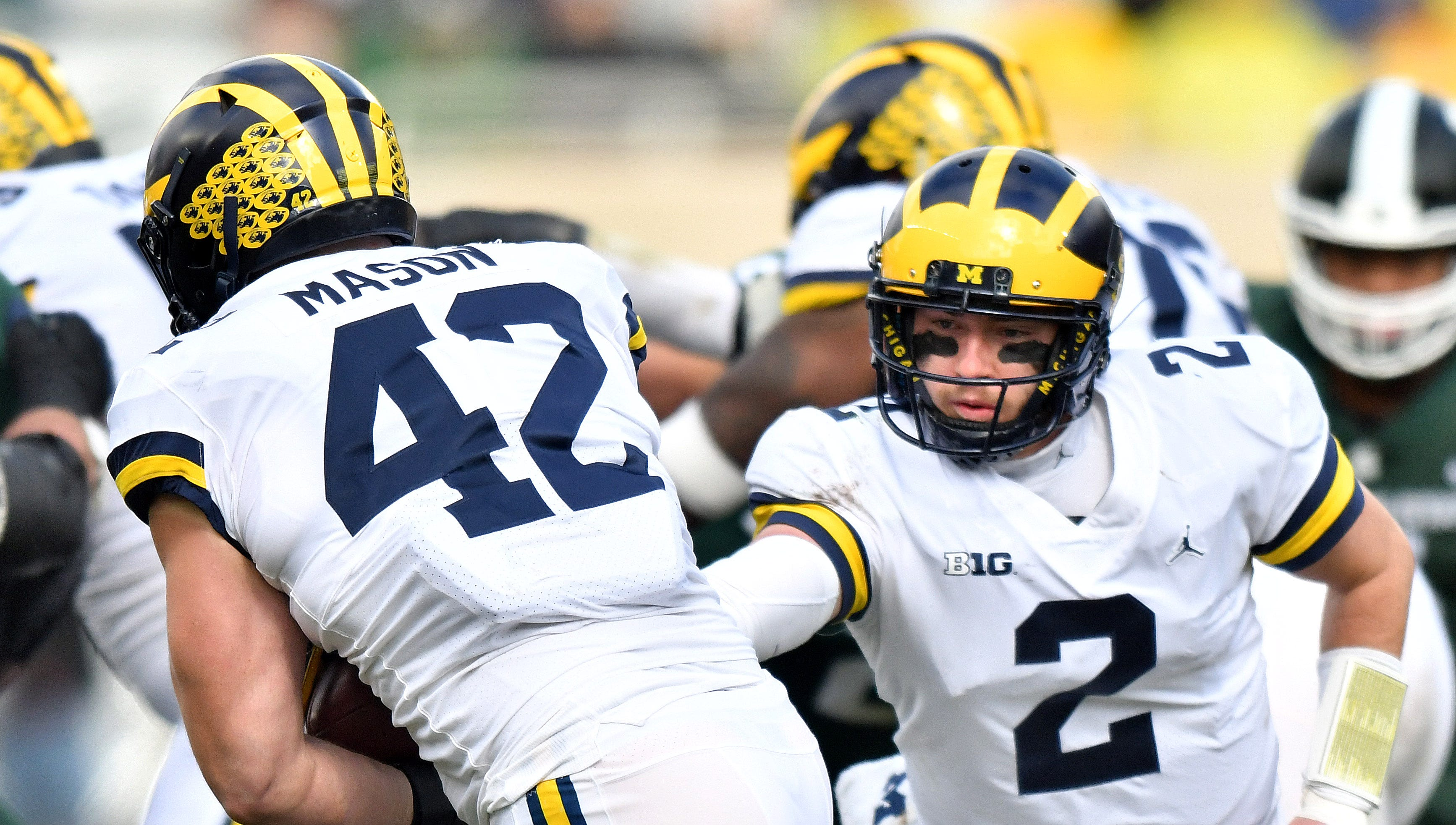 Wolverine quarterback Shea Patterson hands the ball to fullback Ben Mason (42), who rumbles for a first down in the second quarter.