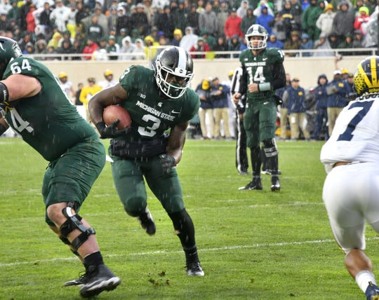 LJ Scott takes the ball from Brian Lewerke (background) and runs for a first down against Michigan.