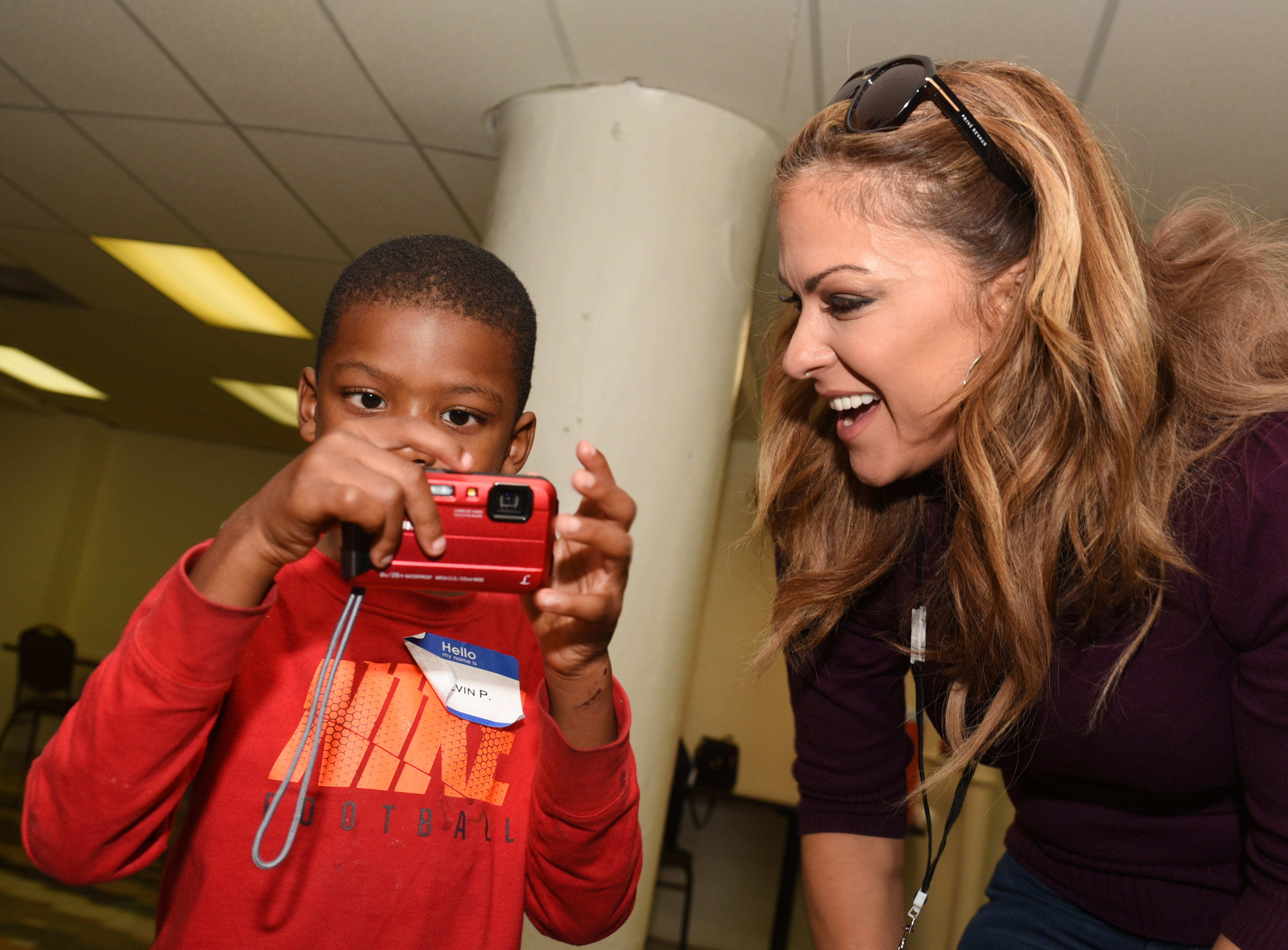 Fox 2 reporter Taryn Asher (right) works with Kevin P as they view images taken during a lesson given by famed  photographer Linda Solomon for homeless children in Detroit on October 20, 2018.