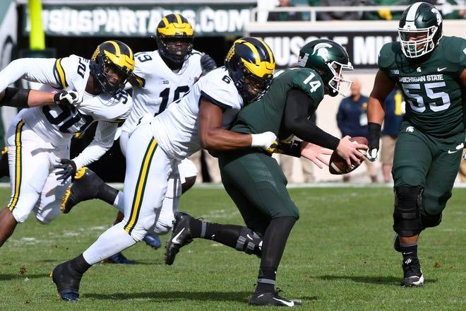 Michigan's Josh Uche (6) sacks Michigan State quarterback Brian Lewerke in the first quarter on Saturday.
