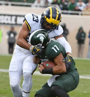Michigan's Tyree Kinnel takes down Michigan State's Connor Heyward in the third quarter on Saturday.