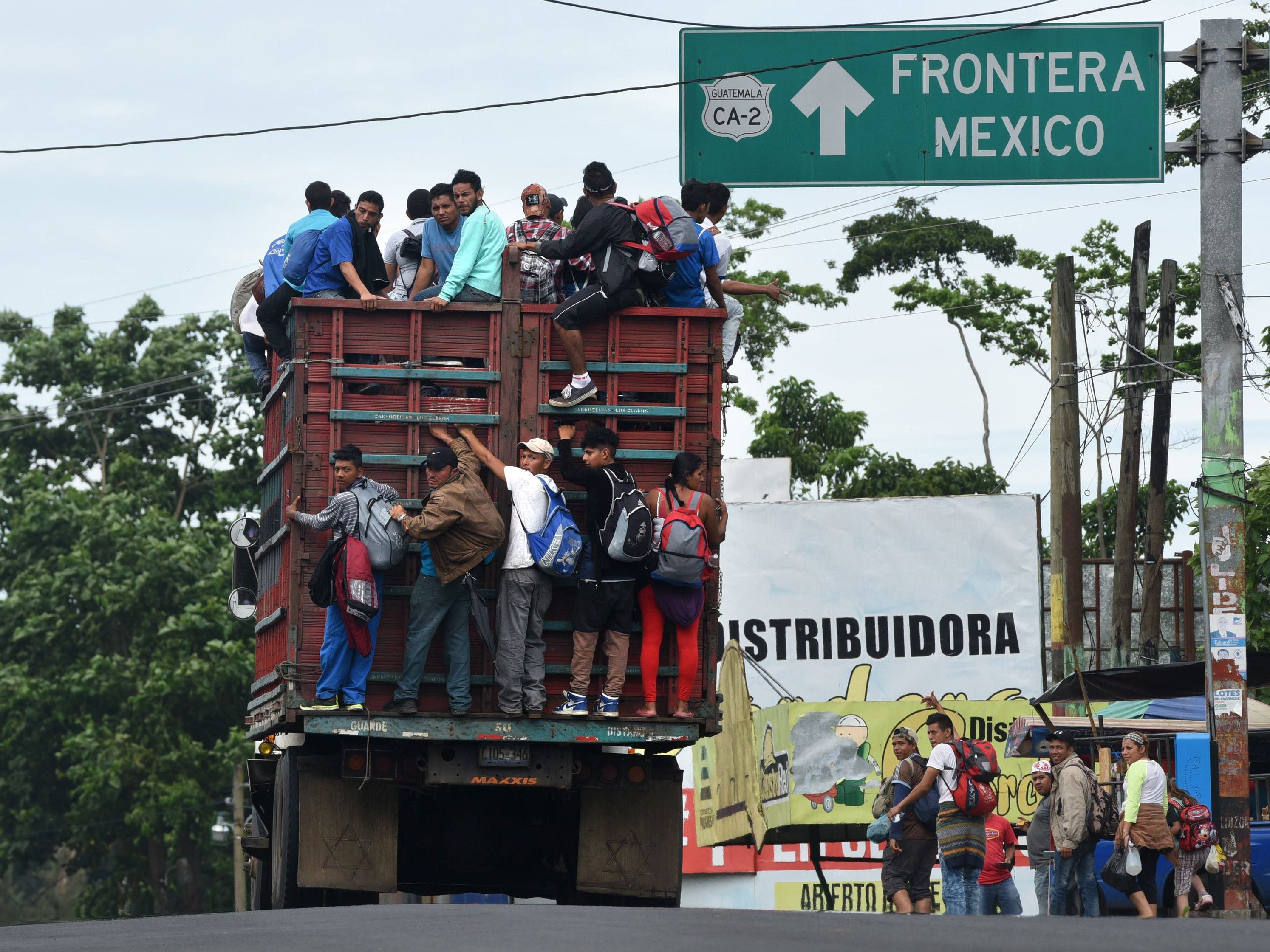 Honduran migrants ride on a truck toward Tecun Uman, Guatemala, on the border with Mexico, to take part in a caravan heading to the U.S., on Oct. 19, 2018. Honduran migrants who have made their way through Central America were gathering at Guatemala's northern border with Mexico on Friday, despite President Donald Trump's threat to deploy the military to stop them from entering the United States.