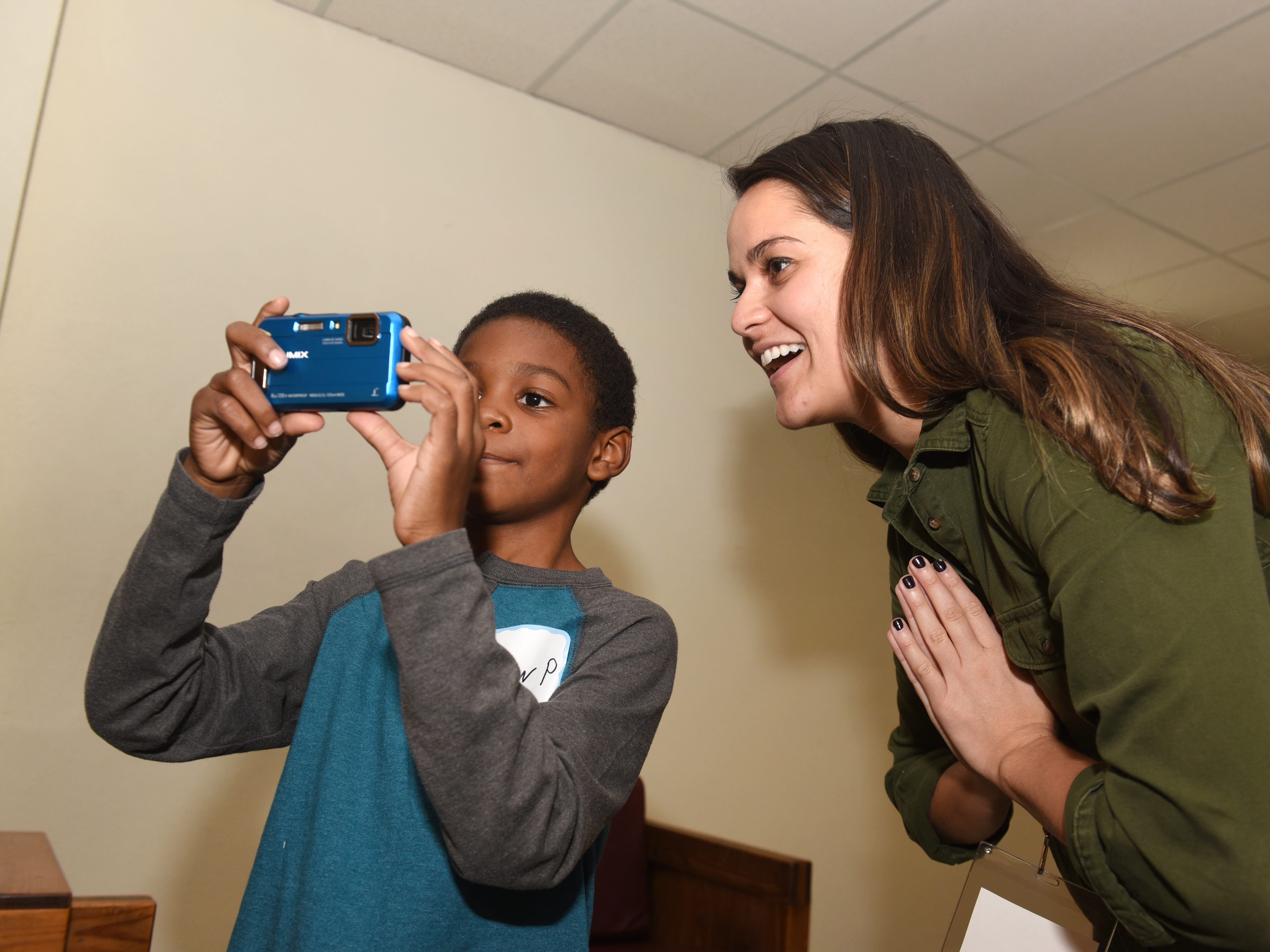 Community mentor Alexis Ahee (right) smiles as she assist Andrew P. as they take pictures in Detroit on October 20, 2018.