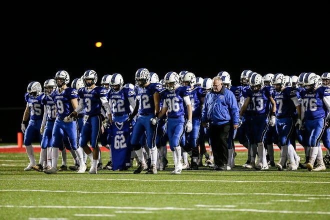 St. Mary's Springs Academy football senior team captains Mitchell Waechter (3) and Jacob Schrauth (72) lead the team out on the field in Lomira on Friday, carrying the jersey of Trent Schueffner.