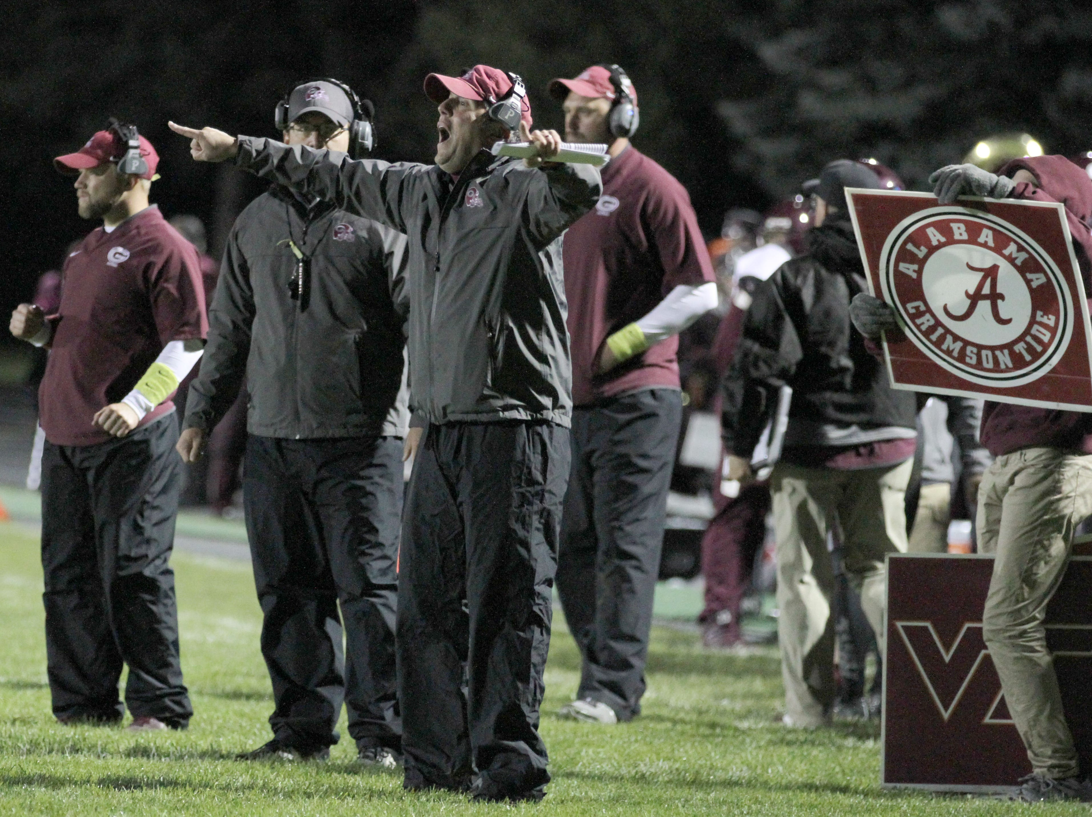Genoa coach Paul Patterson challenges the defense for a late first half goal line stand against Eastwood.