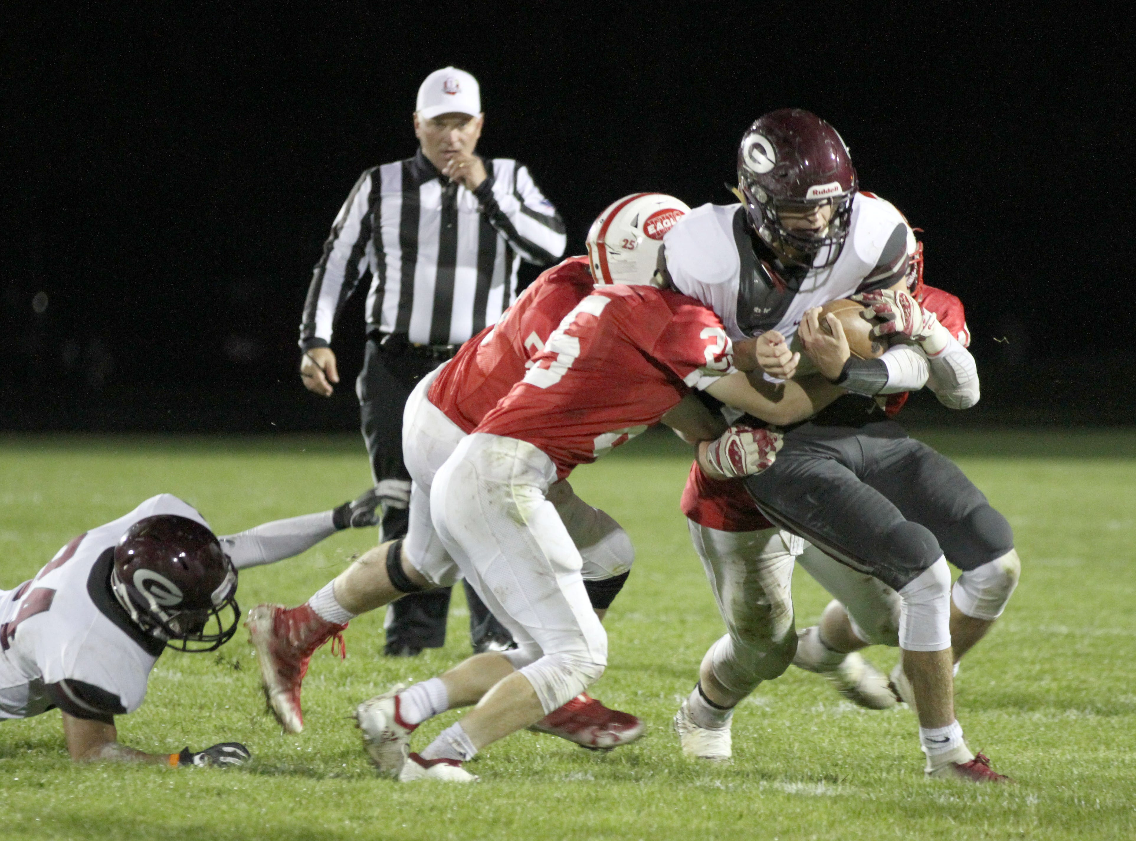 Genoa's Jacob Plantz is tackled by three Eastwood defenders.