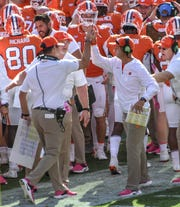 Clemson receiver coach Jeff Scott gives Dabo Swinney a high five after wide receiver Tee Higgins (5) caught a ball for a touchdown during the first quarter in Memorial Stadium on Saturday, October 20, 2018.
