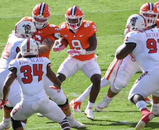 Clemson running back Travis Etienne (9) runs near NC State safety Tim Kidd-Glass (34)  during the first quarter in Memorial Stadium on Saturday, October 20, 2018.