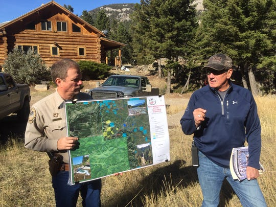 Bryan Golie of Montana Fish, Wildlife and Parks, left, says he's never seen a land purchase that would provide as much public benefit as the Falls Creek deal. He holds a map of the area while Mike Mueller of the Rocky Mountain Elk Foundation, which is buying the property from Dan Barrett, explains its importance.