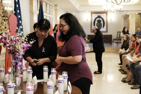Roxanne Aguon and Cynthia Cabot of the Guam Coalition Against Sexual Assault and Family Violence light a candle at the 2018 Silent Witness Ceremony at Government House Oct. 19, 2018.