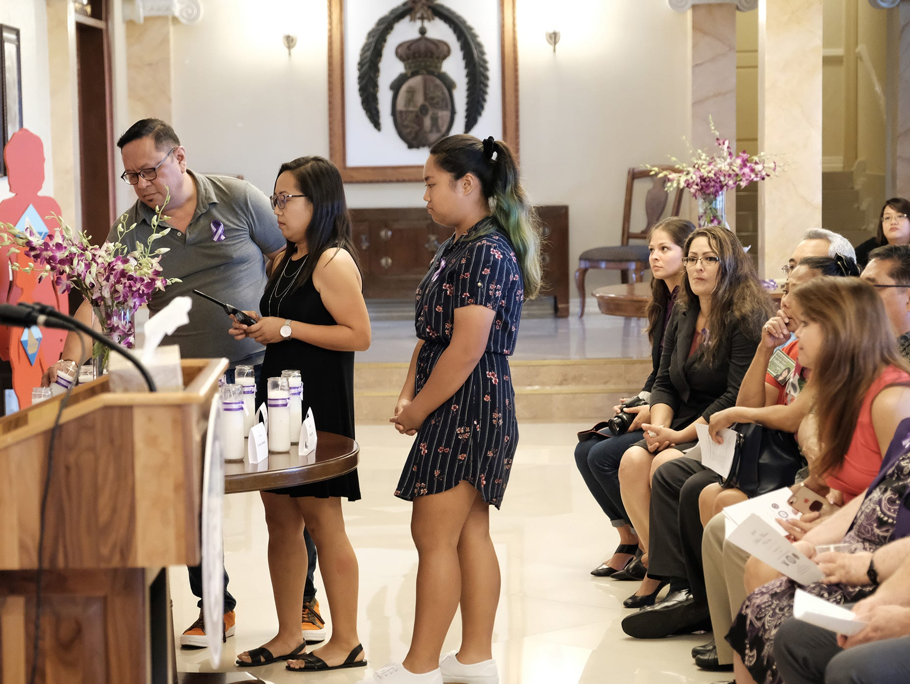 Peter Constantino, Jennifer Constantino and Cayla Constantino  light a candle for Lourdes Constantino Mallo at the 2018 Silent Witness Ceremony at Government House Oct. 19, 2018.