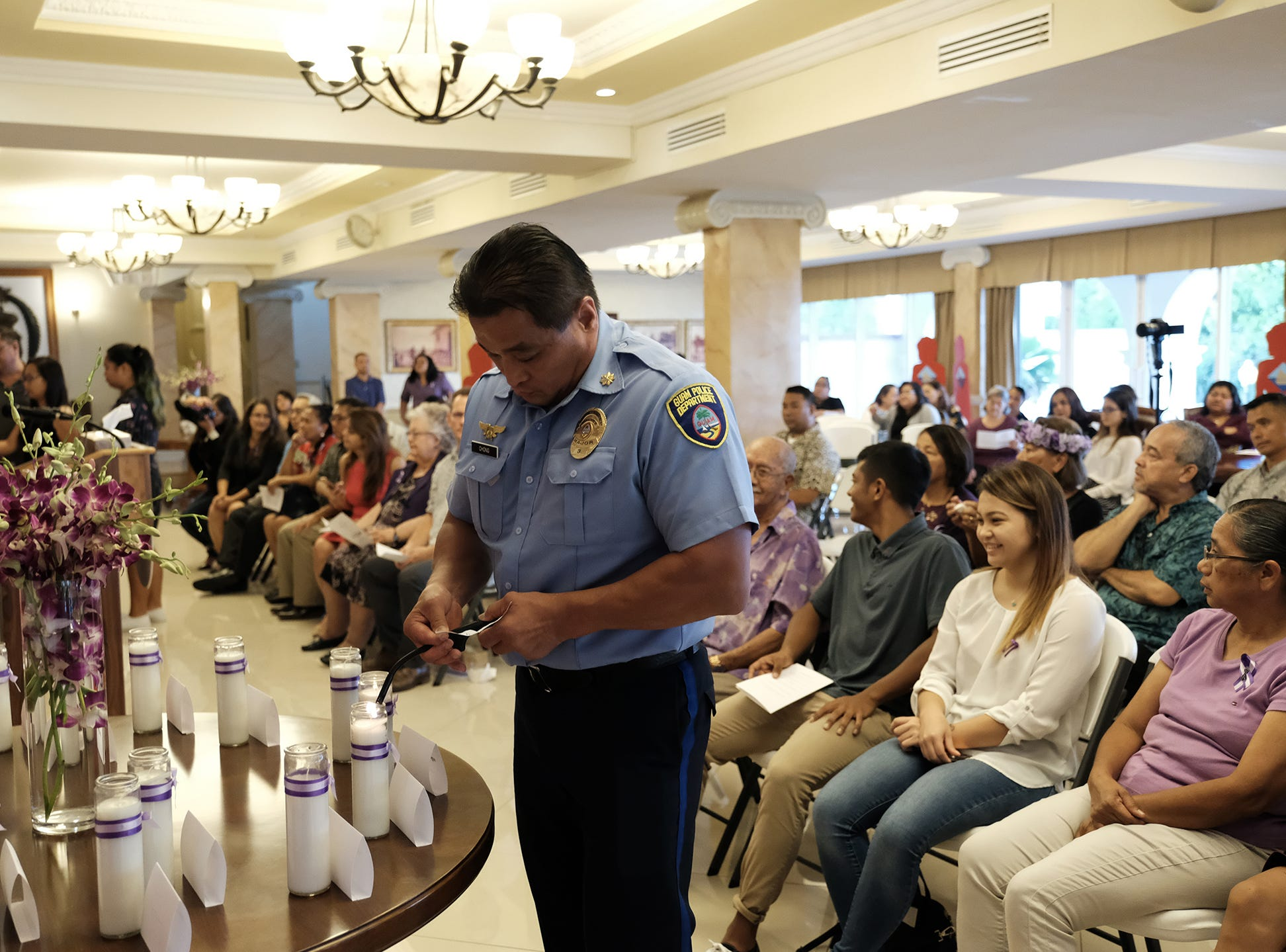 Guam Police Major Manny Chong lights a candle at the 2018 Silent Witness Ceremony at Government House Oct. 19, 2018.