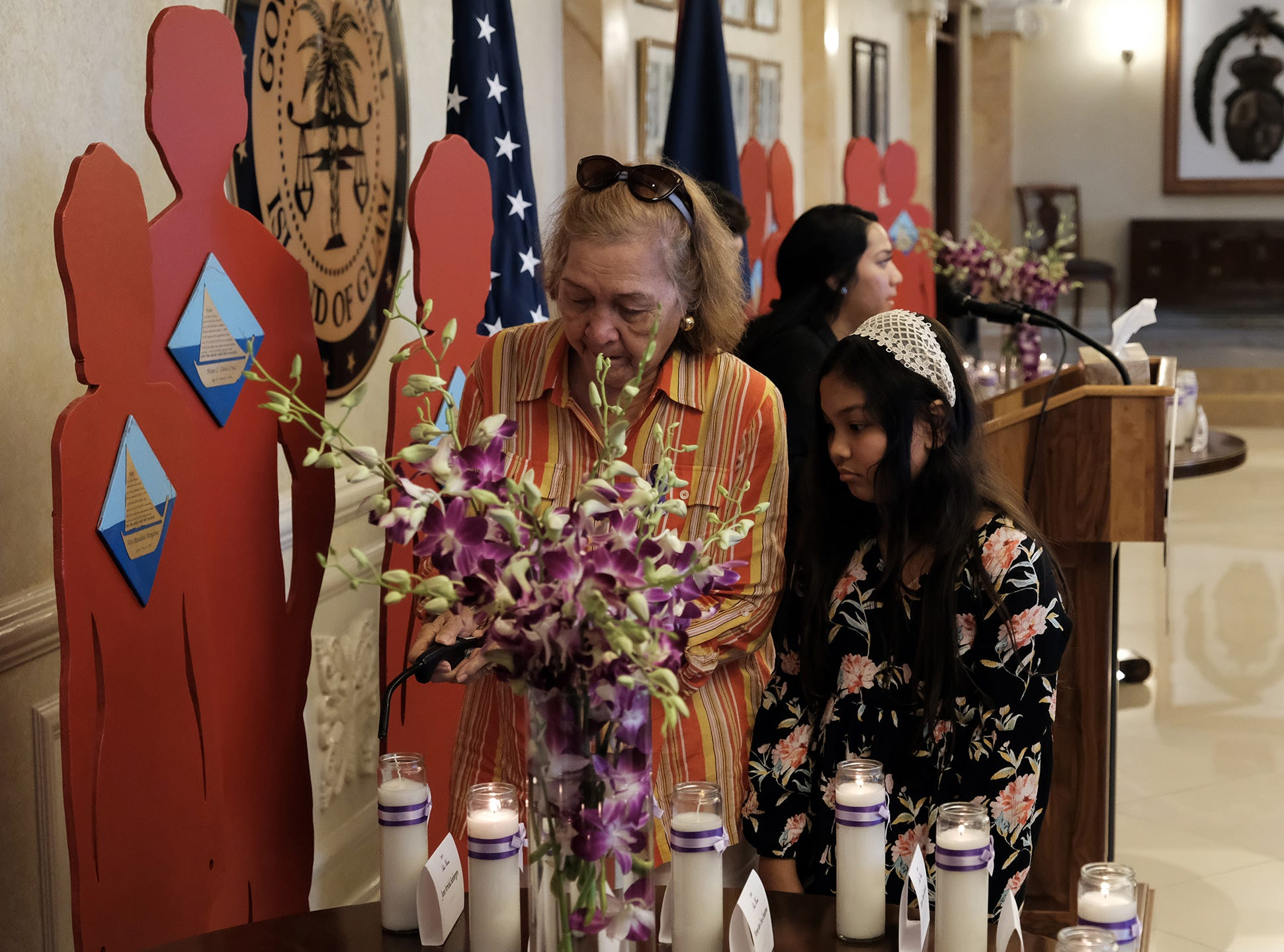 Ana D. Cruz and Kiersten Fernandez, 9, light a candle for June Arriola Sanbergen at the 2018 Silent Witness Ceremony at Government House Oct. 19, 2018.