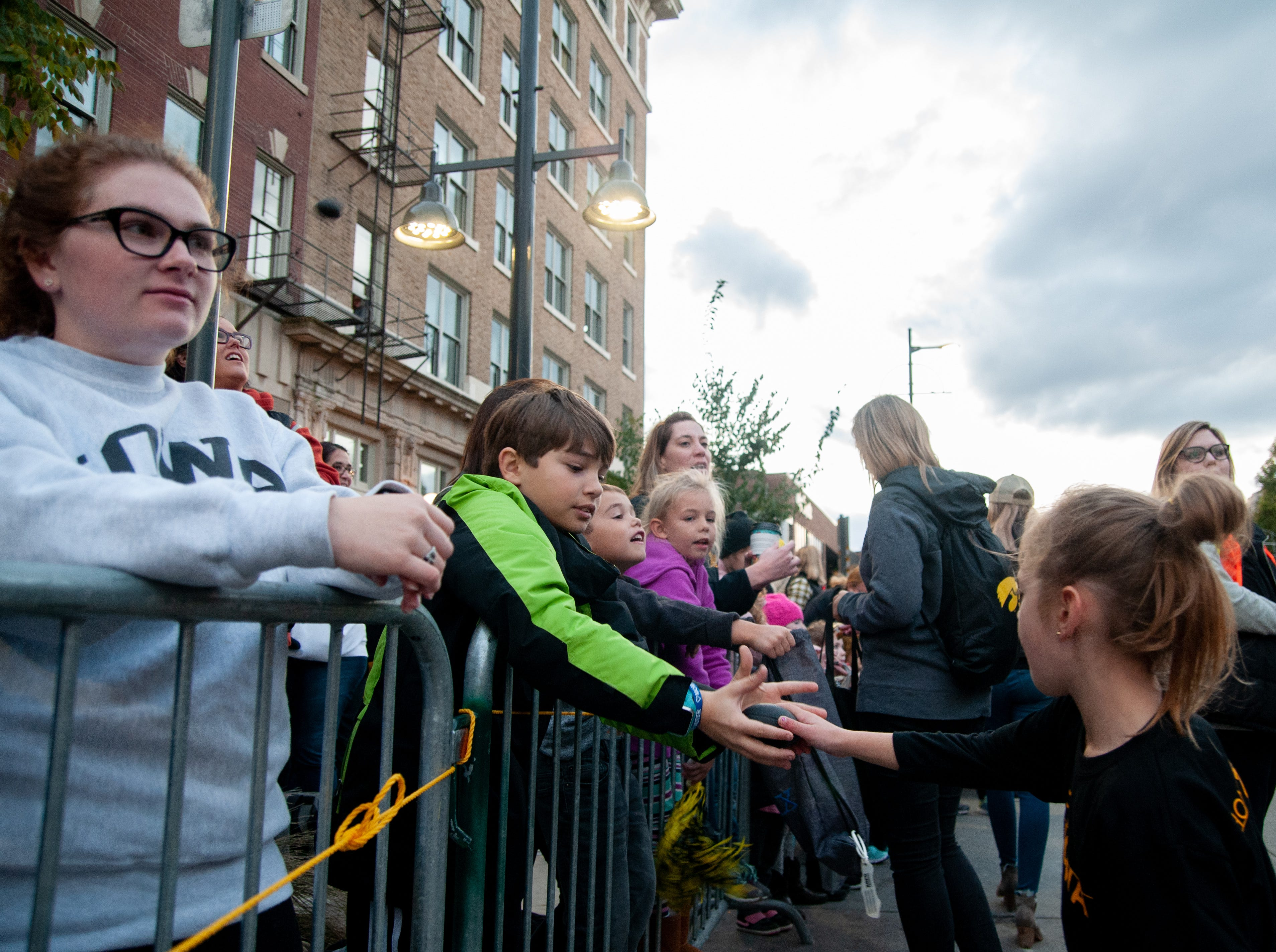 Henry Vanscoyk, 10, receives a foam football during the 2018 Homecoming parade, Friday, Oct. 19, 2018, in Iowa City.