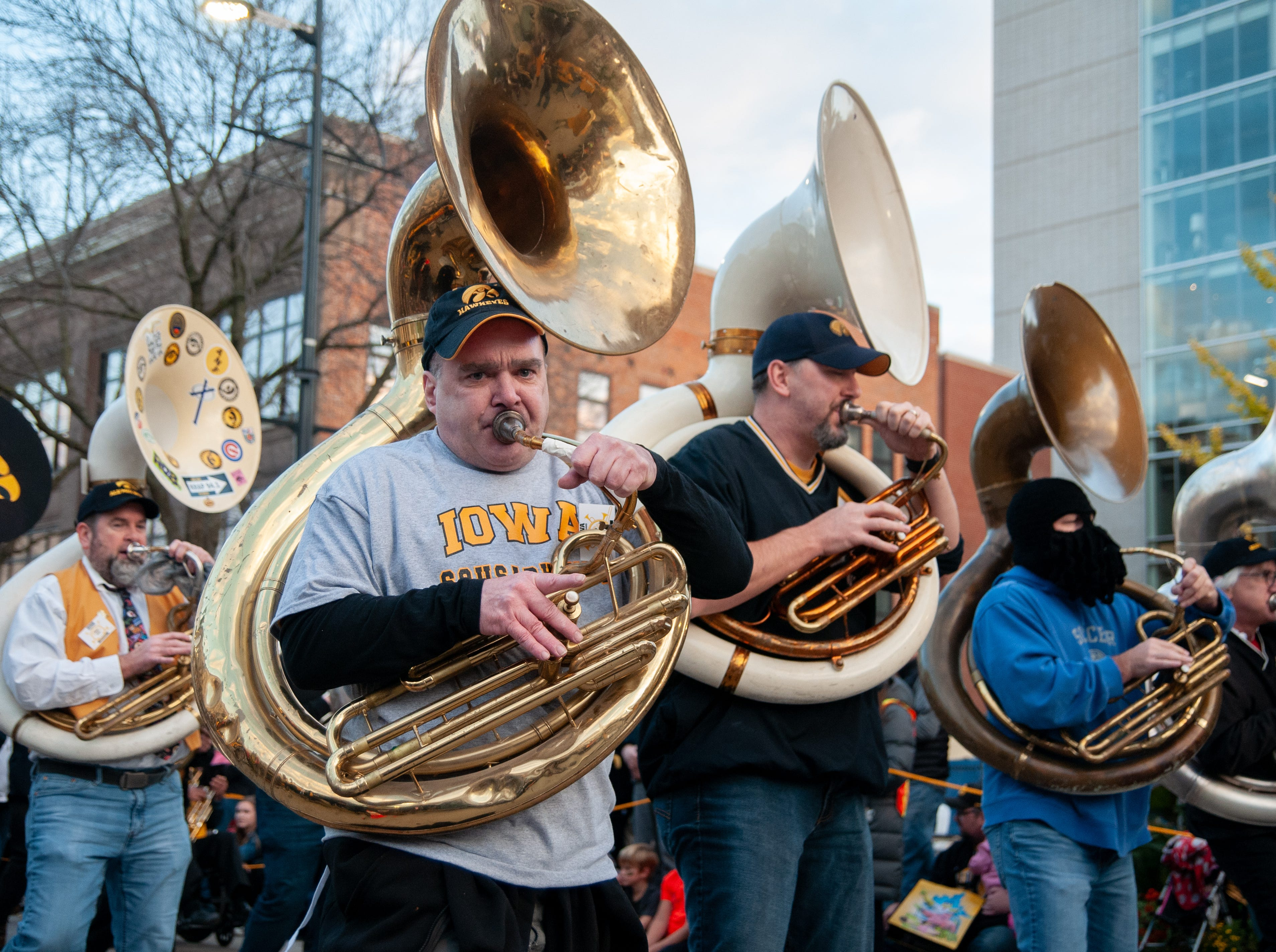 """Hawkeye Alumni Marching Band members perform """"Iowa Fight Song""""  in the 2018 Homecoming parade, Friday, Oct. 19, 2018, in Iowa City."""