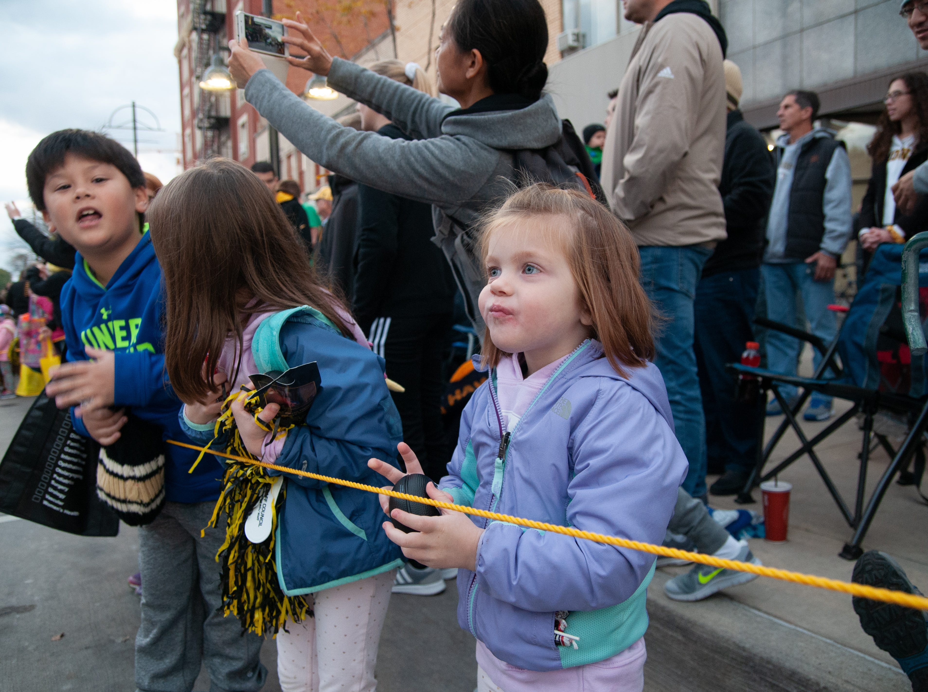 Maggie Boersma, 3, chews candy during the 2018 Homecoming parade, Friday, Oct. 19, 2018, in Iowa City.